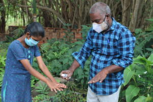 Sandiya is disinfecting her hands with our team member, Gopal